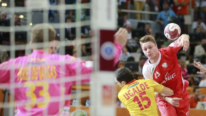 Jurecki of Poland shoots against goalkeeper de Vargas past Ugalde of Spain during their third-place match of the 24th Men's Handball World Championship in Doha