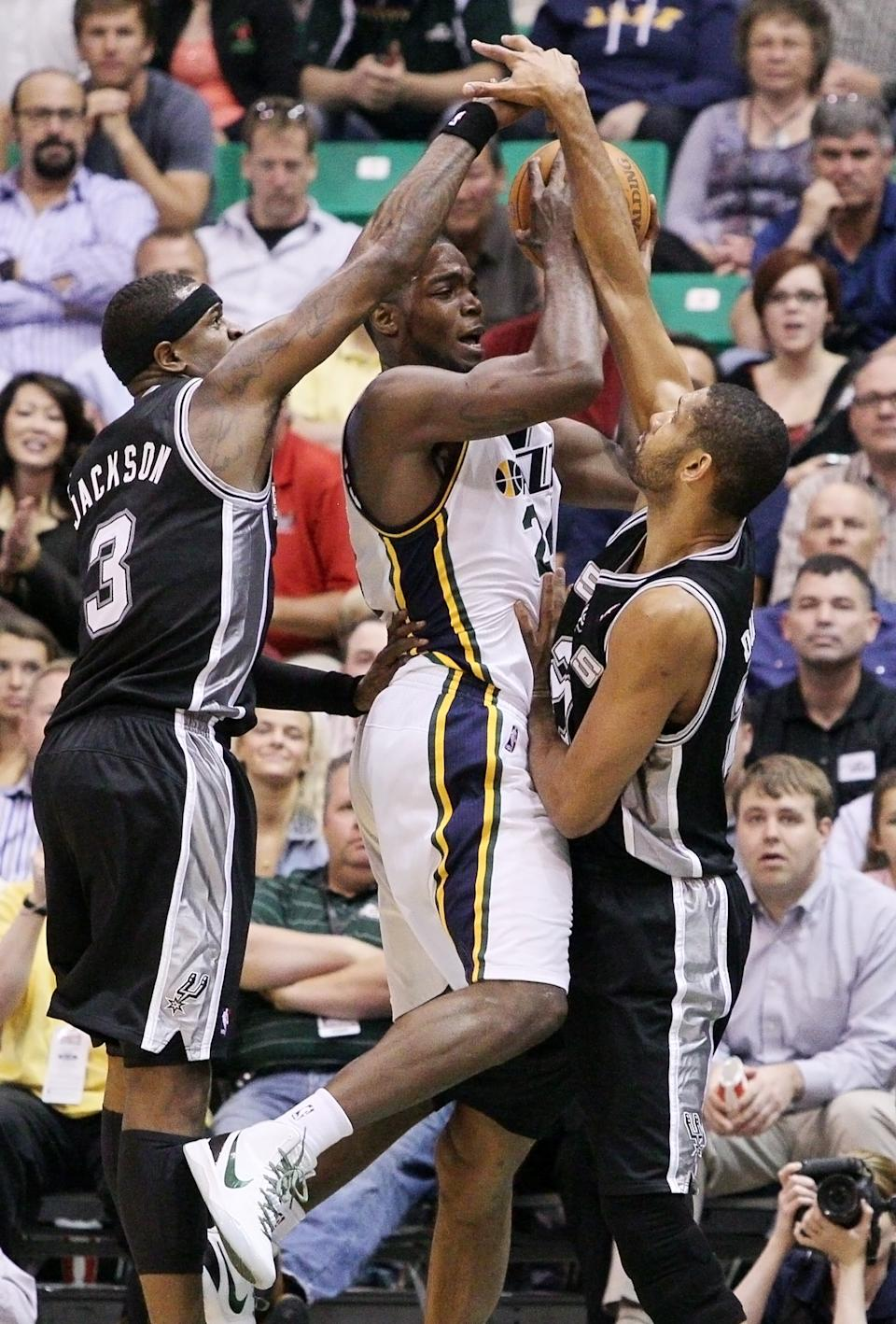 San Antonio Spurs guard Stephen Jackson (3) and center Tim Duncan (21) double team Utah Jazz  forward Paul Millsap (24) during the first half of Game 4 in the first-round NBA basketball playoff series, Monday, May 7, 2012, in Salt Lake City. (AP Photo/Colin E Braley)