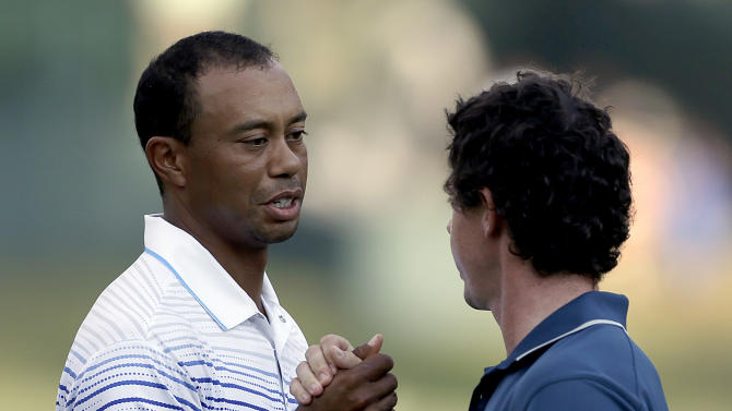 Tiger Woods, left, and Rory McIlroy, of Northern Ireland, clasp hands on the 18th green after finishing the first round of the Tour Championship golf tournament Thursday, Sept. 20, 2012, in Atlanta. (AP Photo/David Goldman)