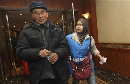 A relative of a passenger of Malaysia Airlines flight MH370 is escorted by a caregiver from Malaysia Airlines as they walk in a corridor at a hotel in Beijing