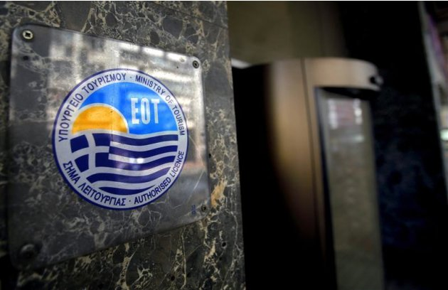A Greek Ministry of Tourism licence is seen outside the closed-down Acropol hotel in central Athens