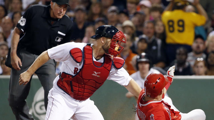 Los Angeles Angels' Mike Trout slides safely into home to score on Josh Hamilton's sacrifice fly as Boston Red Sox catcher David Ross puts on a late tag in the fifth inning of a baseball game at Fenway Park in Boston, Wednesday, Aug. 20, 2014. (AP Photo/Elise Amendola)