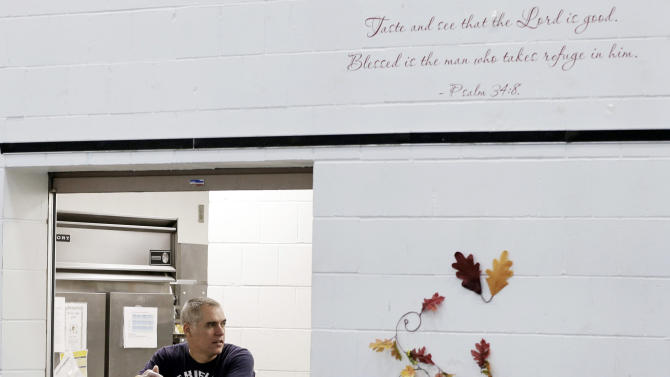 In this Nov. 14, 2013 photo, a Bible verse is written on the wall where chef Jeff Ansorge waits to serve lunch at the Salvation Army Eastside Corp Community Center in St. Paul, Minn. Ansorge, who used to command a staff of 17 at a posh downtown Minneapolis restaurant making nearly $80,000 a year, gave it all up to become the cook in charge of a Salvation Army soup kitchen where the meals are free. (AP Photo/Jim Mone)