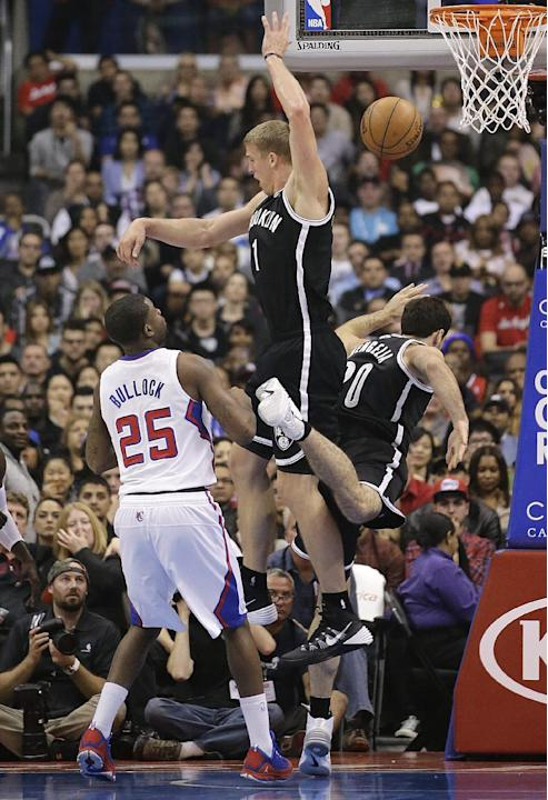 Brooklyn Nets' Mason Plumlee, center, jumps for a rebound after Tornike Shengelia, right, of Georgia, missed the shot during the first half of an NBA basketball game against the Los Angeles Clippers o