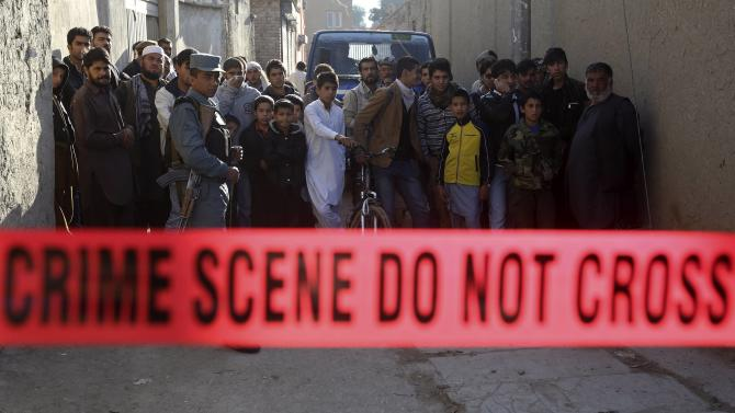 An Afghan policeman secures the area as residents stand near a bus, which was hit by a remote-controlled bomb, at the site of an incident in Kabul