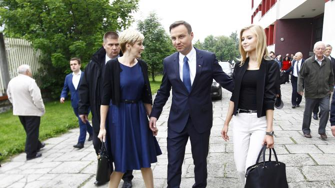 Duda, presidential candidate of the Law and Justice Party (PiS), walks with his wife Agata and their daughter Kinga as they leave a polling station in Krakow
