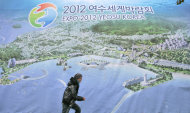 FILE- In this Tuesday, Dec. 4, 007 file photo, a South Korean man walks past a huge banner of Yeosu Expo 2012 at downtown of Yeosu, south of Seoul, South Korea. About 100 countries and 8 million visitors are expected for the Expo. (AP Photo/ Lee Jin-man, FILE)