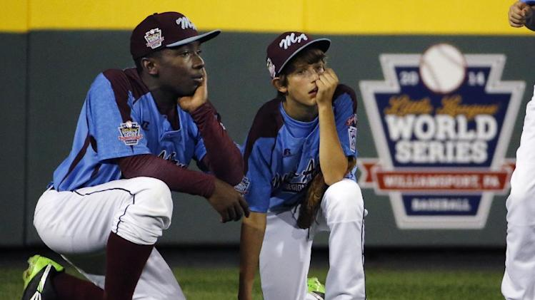 Philadelphia outfielders Carter Davis, right, and Zion Spearman kneel in the outfield during a pitching change in the third inning of a United States semi-final baseball game against Las Vegas at the Little League World Series tournament in South Williamsport, Pa., Wednesday, Aug. 20, 2014. Las Vegas won 8-1. (AP Photo/Gene J. Puskar)