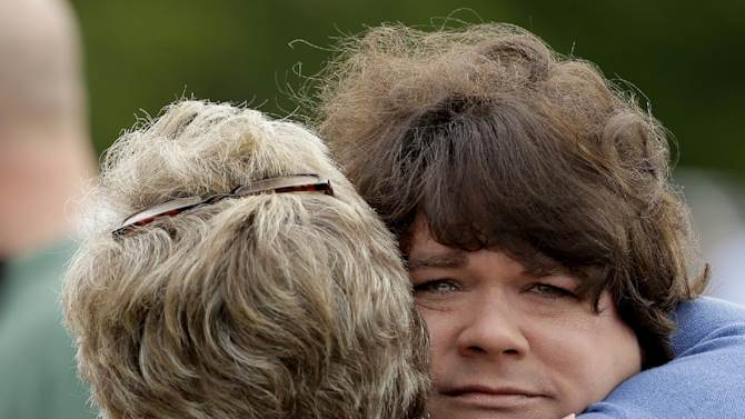 Lisa Crowder, facing camera, is hugged by a friend before a service for the First Baptist Church held in a field Sunday, April 21, 2013, four days after an explosion at a fertilizer plant in West, Texas. Crowder's home was destroyed after a massive explosion at the West Fertilizer Co. Wednesday night that killed 14 people and injured more than 160. (AP Photo/Charlie Riedel)
