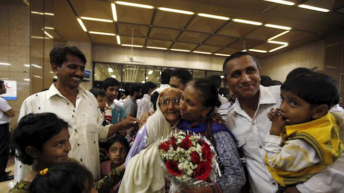 Pakistani woman with a bouquet, who was stranded in Yemen, greets her relatives upon her arrival with others, at Jinnah International Airport Karachi