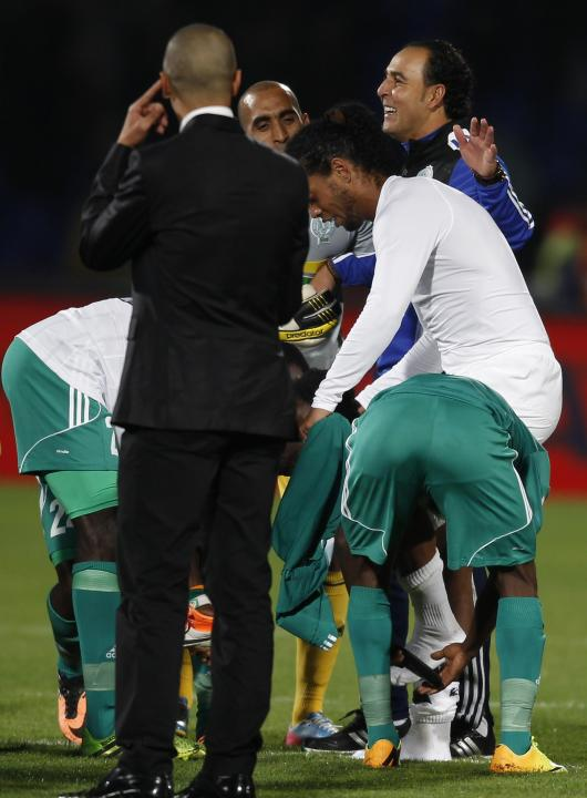 Raja Casablanca players take off the shoes of Atletico Mineiro's Ronaldinho after their FIFA Club World Cup semi-final match at Marrakech stadium