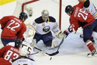 Buffalo Sabres goalie Ryan Miller (30) looks for the puck against Washington Capitals right wing Mike Knuble (22) and Matt Hendricks (26) during the first period of an NHL hockey game, Friday, Dec. 30, 2011, in Washington. Buffalo Sabres center Jochen Hecht (55) and Washington Capitals center Jay Beagle (83) trail the play. (AP Photo/Nick Wass)