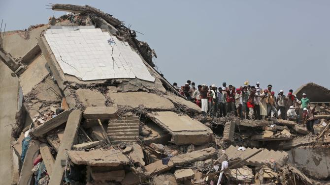 Bangladeshi rescuers work at the site of a building that collapsed Wednesday in Savar, near Dhaka, Bangladesh, Friday, April 26, 2013. By Friday, the death toll reached at least 270 people as rescuers continued to search for injured and missing, after a huge section of an eight-story building that housed several garment factories splintered into a pile of concrete. (AP Photo/Kevin Frayer)