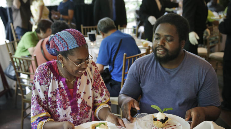 """Sharon Robinson, left, and Roy Gantt, both residents of the New York City Rescue Mission, look over their just served desserts at The Loeb Boathouse restaurant in New York, Wednesday, June 25, 2014. Recycling magnate Chen Guangbiao, known for his sometimes eccentric gestures served up a fancy lunch Wednesday to hundreds of homeless New Yorkers at a Central Park restaurant and serenaded them with """"We are the World."""" (AP Photo/Seth Wenig)"""
