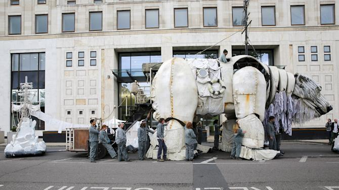Environmental activist stand next to a giant-sized model of a polar bear during a protest in central London