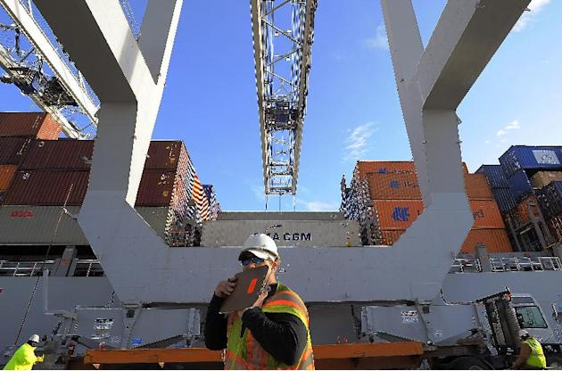 In this Monday, Jan. 2, 2014, photo, a dock worker communicates on a walkie-talkie while a ship to shore crane loads containers onto a ship at the Georgia Ports Authority Garden City terminal, in Sava