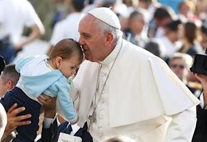 Pope Francis kisses a baby as he arrives to lead the weekly audience in Saint Peter's Square at the Vatican