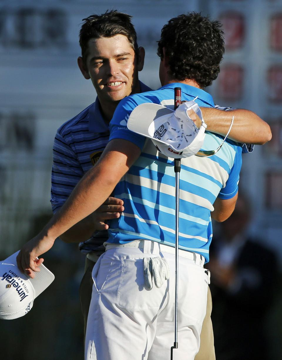 Louis Oosthuizen, left, of South Africa, hugs Rory McIlroy, right, of Northern Ireland, after McIlroy won the Deutsche Bank Championship PGA golf tournament at TPC Boston in Norton, Mass., Monday, Sept. 3, 2012. Oosthuizen finished second. (AP Photo/Michael Dwyer)