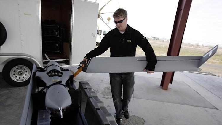 This photo taken March 26, 2013, shows flight test pilot Alex Gustafson dismantling a Insitu ScanEagle unmanned aircraft after a flight in Arlington, Ore.  It's a good bet that in the not-so-distant future aerial drones will be part of Americans' everyday lives, performing countless useful functions. A far cry from the killing machines whose missiles incinerate terrorists, these generally small unmanned aircraft will help farmers more precisely apply water and pesticides to crops, saving money and reducing environmental impacts. They'll help police departments to find missing people, reconstruct traffic accidents and act as lookouts for SWAT teams. They'll alert authorities to people stranded on rooftops by hurricanes, and monitor evacuation flows.  (AP Photo/Don Ryan)