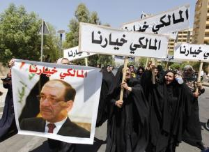 People hold a portrait of Nuri al-Maliki and signs as they gather in support of him in Baghdad