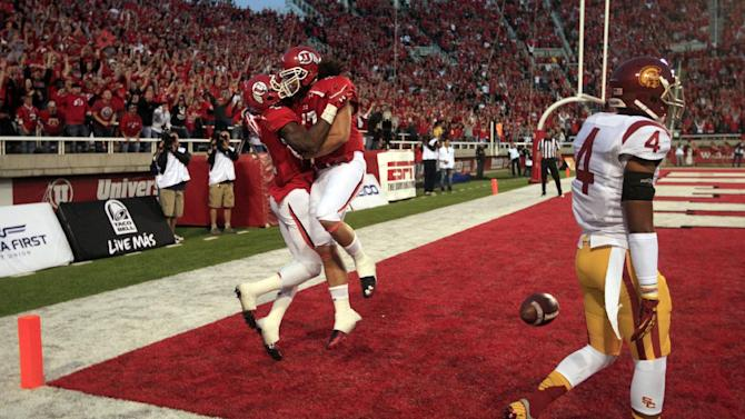 Utah wide receiver Kenneth Scott, left, celebrates with teammate David Rolf after scoring while Southern California cornerback Torin Harris (4) walks off the field in the first quarter during an NCAA college football game Thursday, Oct. 4, 2012, in Salt Lake City.  (AP Photo/Rick Bowmer)