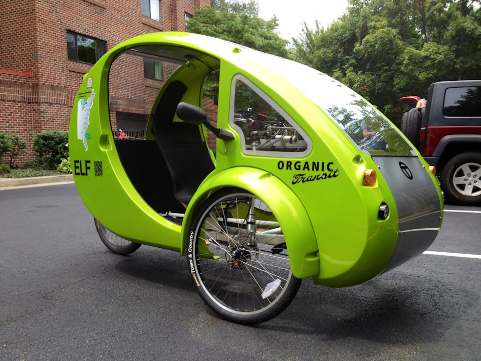 "This photo taken July 24, 2013 shows the Organic Transit's ELF bike in a parking lot in Reston, Va. It's the closest thing yet to Fred Flintstone's footmobile _ only with solar panels and a futuristic shape. It's an ""Organic Transit Vehicle,"" a car-bicycle blend also known as an ELF bike, and 65-year-old family therapist Mark Stewart is taking it on a 1,200-mile journey along the East Coast Greenway, a bike and pedestrian trail that runs from Florida to Canada. (AP Photo/Valerie Bonk)"
