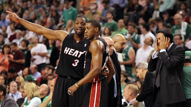 Miami Heat's Dwyane Wade (3) and Mario Chalmers confer on the court, while coach Eric Spoelstra reacts at right during the first half against the Boston Celtics in Game 3 of the NBA basketball playoffs Eastern Conference finals, Friday, June 1, 2012, in Boston. (AP Photo/Miami Herald, Al Diaz) MAGS OUT