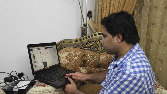 Palestinan Khalel Shreateh sits in front of his his computer at his home in the West Bank town of Yatta south of Hebron, Monday, Aug. 19, 2013. After discovering a privacy bug on Facebook, unemployed Palestinian programmer Khalil Shreateh said he just wanted to collect the traditional $500 bounty the social network giant offers to those who voluntarily expose its glitches. But when Facebook ignored his first two reports, Shreateh took his message to the top and hacked into CEO Mark Zuckerberg's personal page to prove his point. (AP Photo/Nasser Shiyoukhi)