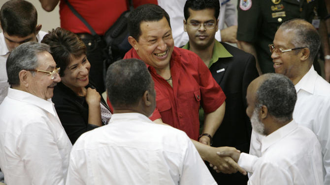 FILE - In this Dec. 21, 2007 file photo, Venezuela's President Hugo Chavez, top center, shakes hands with Haiti's President Rene Preval as Cuba's acting President Raul Castro, far left, looks on during the inauguration of the IV Petrocaribe summit in Cienfuegos, Cuba. Now nervous Cubans are worrying about a return of hard times following the March 5, 2013 death of Chavez, whose billions of dollars of oil largesse helped the island's economy function. More than a dozen countries besides Cuba in Latin America and the Caribbean, many of them economic minnows, have benefited to the tune of billions of dollars from the Petrocaribe pact, created in 2005 with the goal of unifying the regional oil industry under Venezuelan leadership and countering U.S. influence. (AP Photo/Dado Galdieri, File)