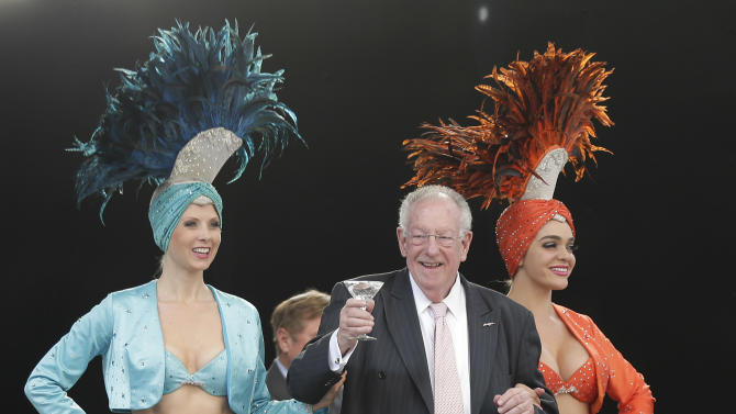 """Oscar Goodman walks onto the First Street Stage accompanied by two Las Vegas showgirls to kick off a car show at the Fremont Street Experience, Friday, May 17, 2013, in Las Vegas. The former Las Vegas mayor branded the city with a larger than life persona. And now he's branded himself again with a memoir. In """"Being Oscar--From Mob Lawyer to Mayor of Las Vegas, Only in America,"""" Goodman tells all from his days as a lawyer representing members of the mob to his three terms as the """"happiest mayor in the universe."""" (AP Photo/Julie Jacobson)"""
