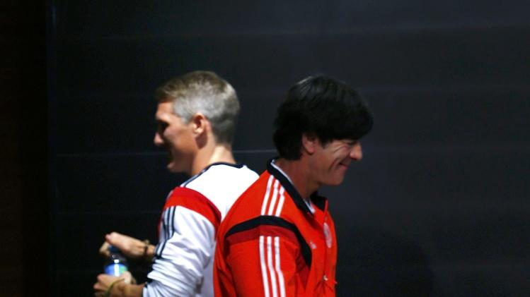 Germany's Schweinsteiger leaves as coach Loew arrives for a news conference at the Maracana stadium in Rio de Janeiro