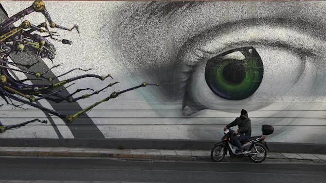 In this photo taken on Thursday Feb. 20, 2014, a motorcyclist passes the work 'Access Control' by Greek street artist iNO, on central Pireos Street in Athens. Greece has attracted international street artists to its capital, due to the availability of commissioned work and relatively lax anti-graffiti law. (AP Photo/Dimitri Messinis)