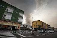 A man rides a motorbike in the town of Gua de Isora as dark clouds of smoke billow from a wildfire on the Spanish Canary Island of Tenerife. Spanish authorities evacuated the town of Vilaflor on the Canary Islands Tuesday as a raging wildfire reached it, an AFP photographer witnessed