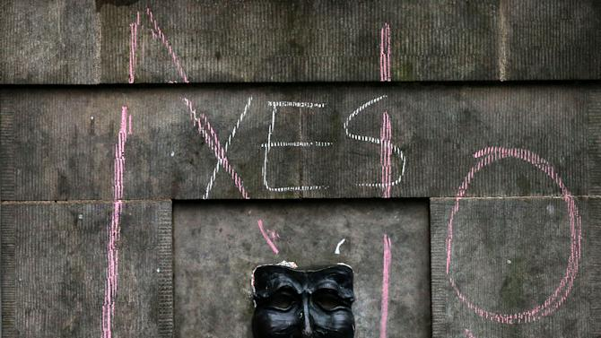 A chalk message for the No campaign is scrawled on top of a Yes message for the Scottish independence referendum are seen on a building on the Royal Mile in Edinburgh, Scotland, Friday, Sept. 19, 2014. Scottish voters have rejected independence and decided that Scotland will remain part of the United Kingdom. The result announced early Friday was the one favored by Britain's political leaders, who had campaigned hard in recent weeks to convince Scottish voters to stay. It dashed many Scots' hopes of breaking free and building their own nation. (AP Photo/Scott Heppell)