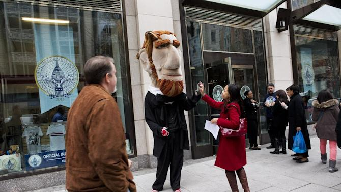 Cleve Mesidor high-fives a man dressed as President Abraham Lincoln as a line forms to enter the Official Inaugural Store during its grand opening in Washington, Friday, Jan. 11, 2013. (AP Photo/Jacquelyn Martin)