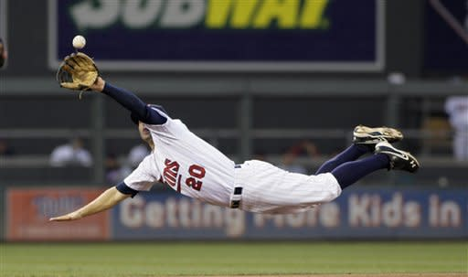 Minnesota Twins shortstop Brian Dozier makes a diving catch on a line drive by Cleveland Indians' Brent Lillibridge during the seventh inning in a baseball game, Saturday, July 28, 2012, in Minneapolis. Minnesota won 12-5. (AP Photo/Paul Battaglia)