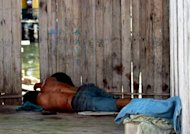 A Sulu gunman who was shot dead, lies on the ground after a shoot-out with soldiers in Simunul village on March 4, 2013. Malaysia vowed to beef up security in the eastern state where at least 26 people have been reported killed after a bizarre invasion by Philippine followers of a self-styled sultan. AFP PHOTO MALAYSIA OUT