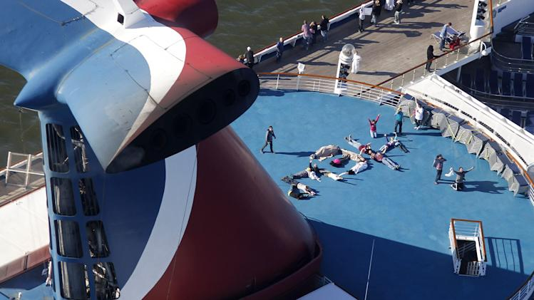 "Passengers spell out the word ""HELP"" aboard the disabled Carnival Lines cruise ship Triumph as it is towed to harbor off Mobile Bay, Ala., Thursday, Feb. 14, 2013. The ship with more than 4,200 passengers and crew members has been idled for nearly a week in the Gulf of Mexico following an engine room fire. (AP Photo/Gerald Herbert)"