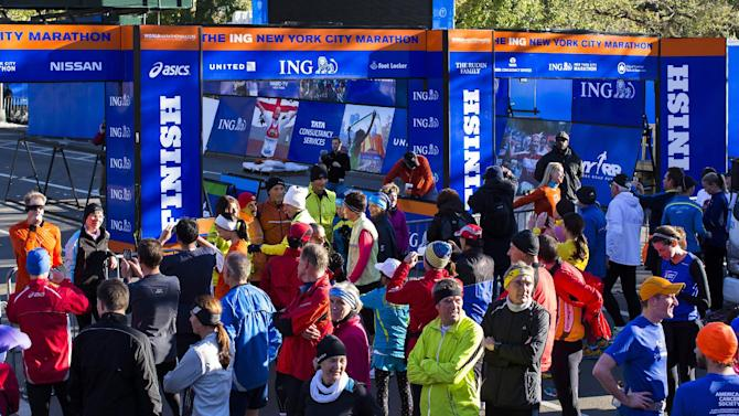 FILE - In this Nov. 3, 2012 file photo, a crowd of runners stands near the barricaded Central Park finish line for the canceled New York Marathon. The increased security will be unmistakable for the Nov. 3, 2013, marathon, from barriers around Central Park to added checkpoints. (AP Photo/ John Minchillo, File)