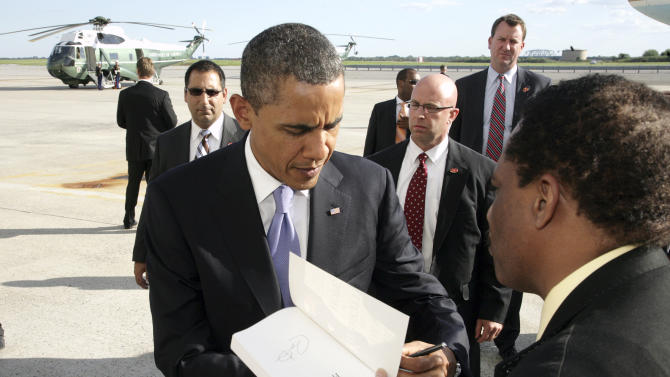 President Barack Obama signs a copy of his book for one of the well wishers who came to greet him as he arrives at John F. Kennedy International Airport in New York, Thursday, Aug. 11, 2011, on his way to fundraisers in Manhattan. (AP Photo/David Karp)