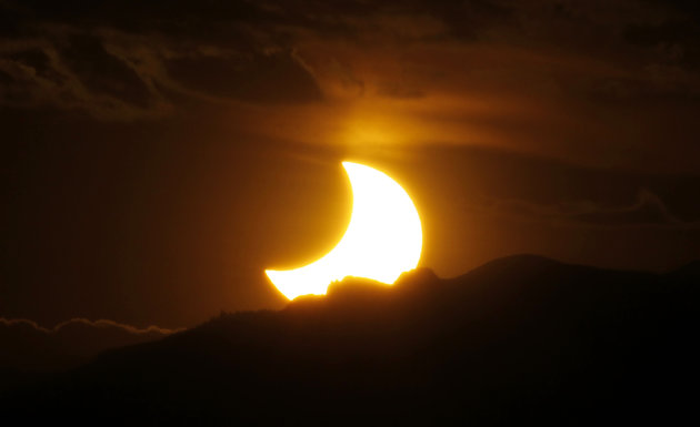 The annular solar eclipse is seen as the sun sets behind the Rocky Mountains from downtown Denver late on Sunday, May 20, 2012. The annular eclipse, in which the moon passes in front of the sun, was visible across Asia as well as the southwest part of the United States. (AP Photo/David Zalubowski)