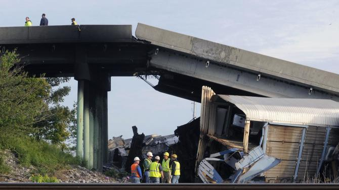 Emergency personnel investigate the Route M overpass at Rockview, Mo., about 10 miles south of Cape Girardeau, Mo., after it collapsed onto the railroad tracks, Saturday, May 25, 2013. The National Transportation Safety Board has launched an investigation into the cause of a cargo train collision that partially collapsed a highway overpass in southeast Missouri, injuring seven people. (AP Photo/The Southeast Missourian, Fred Lynch)