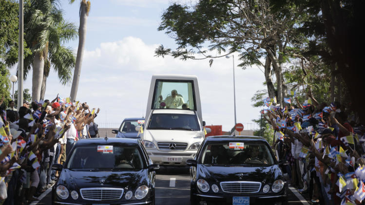 Pope Benedict XVI waves from the popemobile as people gather along the roadside to greet him upon his arrival to Santiago de Cuba, Cuba, Monday March 26, 2012.  (AP Photo/Desmond Boylan, Pool)