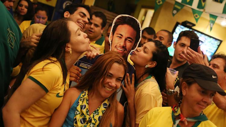 Soccer fans donning Brazil's national team colors pose for a picture with a life-size cutout of soccer star Neymar, after the World Cup match between Brazil and Cameroon, at Copacabana, in Rio de Janeiro, Brazil, Monday, June 23, 2014. Brazil's Neymar scored twice in the first half to lead Brazil to a 4-1 win over Cameroon on Monday, helping the hosts secure a spot in the second round of the soccer World Cup. (AP Photo/Leo Correa)