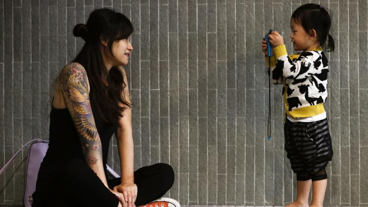 A visitor poses a photo for her daughter at the International Hong Kong China Tattoo Convention in Hong Kong