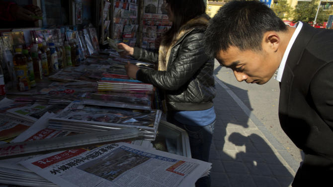"""A man looks over near the front page of a Chinese newspaper showing a photo of the typhoon damage in the Philippines and the white characters on blue which reads """"U.S. and Europe hype up Chinese aid to Philippines as 'Not Generous' """", at a newsstand in Beijing, China, Thursday, Nov. 14, 2013. The outpouring of international aid to the Philippines makes China's contribution for typhoon relief look like a trickle - and that won't help Beijing's campaign to win over neighbors with its soft power. (AP Photo/Ng Han Guan)"""