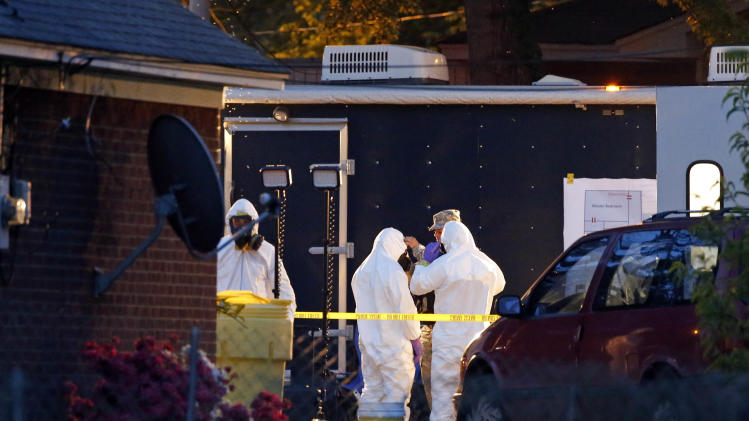 Federal authorities wear hazmat suits as they search the home of Everett Dutschke, Tuesday, April 23, 2013 in Tupelo, Miss., in connection with the recent ricin attacks. No charges have been filed against Dutschke and he hasn't been arrested. (AP Photo/Rogelio V. Solis)