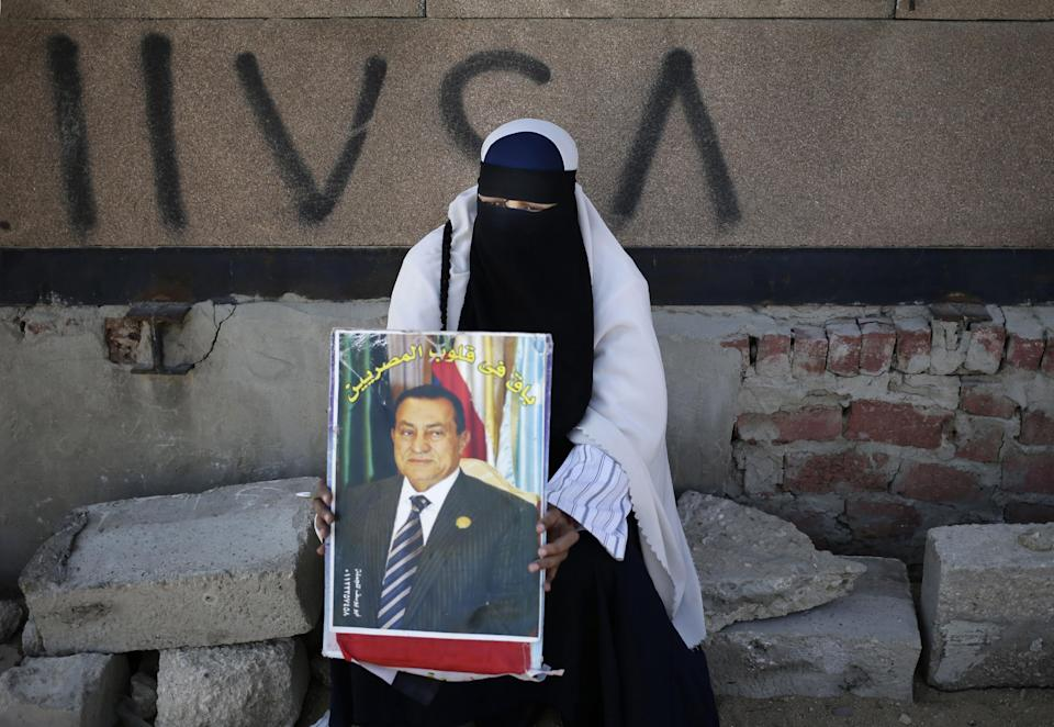 "An Egyptian woman carrying a photo of ousted president Hosni Mubarak as she demonstrates her support for Mubarak at a court in Cairo, Egypt, Saturday, Sept. 14, 2013. The Arabic reads, ""You will still be in the hearts of the Egyptians."" (AP Photo/Hassan Ammar)"