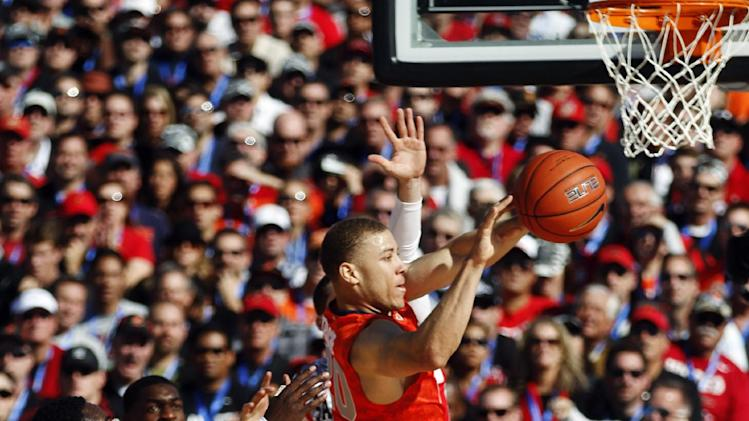 Syracuse guard Brandon Triche passes against three San Diego State defenders during the first half of an NCAA college basketball game on the deck of the USS Midway, Sunday, Nov. 11, 2012, in San Diego. (AP Photo/Lenny Ignelzi)