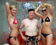 A Chinese man posing with two foreign models during a bikini beach party in Sanya, southern China&#39;s Hainan province, June 30, 2012